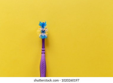 Used toothbrush on a yellow background, the top view. Copy space