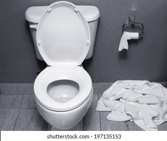 A used towel dropped on the floor next to a toilet.