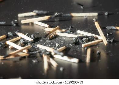 Used wooden matches with the remains of ashes on a black board. Selective focus. Hight contrast.