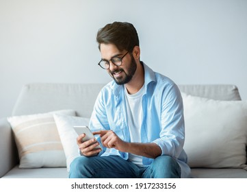 Useful App. Handsome Arab Man In Eyeglasses Using Smatphone While Relaxing On Couch At Home, Eastern Guy Sitting On Sofa In Living Room, Browsing Internet Or Messaging With Friends, Free Space