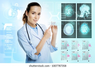 Useful box. Young professional calm doctor standing near the scull xray with a stethoscope on her neck and pointing to a tiny pillbox in her hands