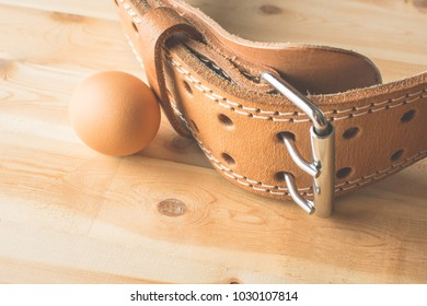 Useful chicken eggs for sports nutrition next to the sports belt.