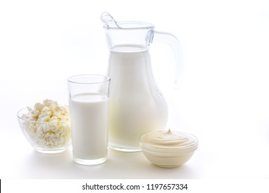 Useful dairy kitchen for bone health. Milk in a jug and a cup on a white background. Fresh sour cream and cottage cheese.