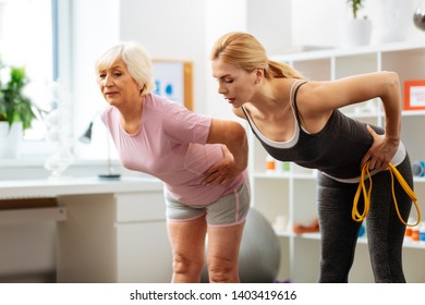 Useful exercise. Good looking pretty woman talking to her patient while leaning forward during training
