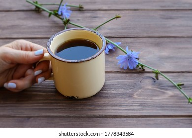 A useful healing drink from chicory root in a metal mug on the table. Alternative to coffee. Cup in a woman's hand.