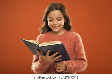 Useful information for her. Girl hold book read story over orange background. Child enjoy reading book. Book store concept. Wonderful free childrens books available to read. Childrens literature.