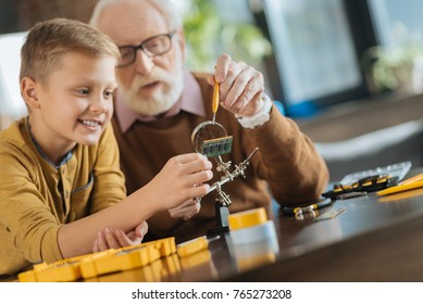 Useful knowledge. Nice positive joyful boy holding a microscheme and smiling while helping his grandfather