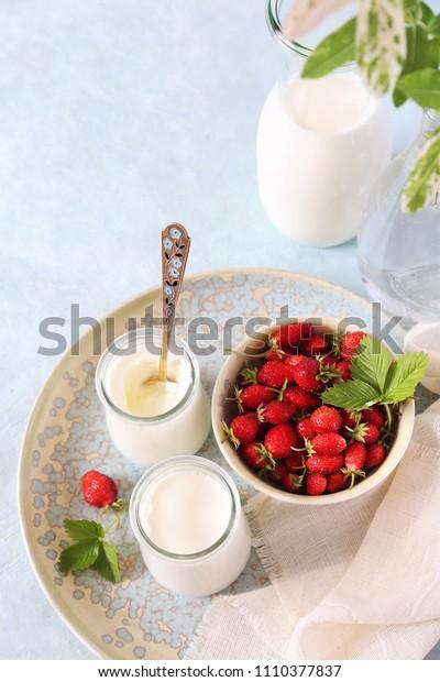 Useful milk dessert: two jars of fresh yogurt, milk and wild strawberry