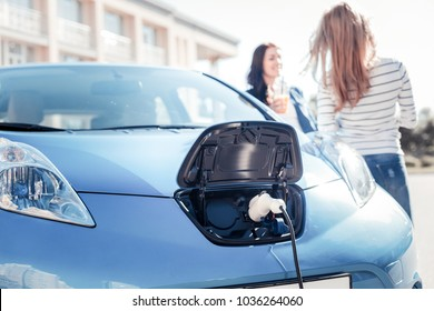 Useful nowadays. Blue comfortable electric car staying near girls and charging.