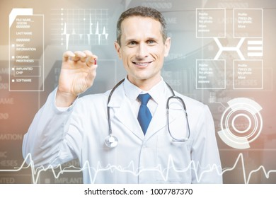 Useful pill. Cheerful emotional qualified doctor looking happy while standing with a stethoscope on his neck and holding a tiny red pill