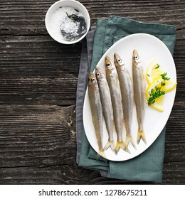 Useful small sea fish. Smelt, sardine, anchovies before cooking with salt, lemon, butter, thyme on a wooden background. Top view