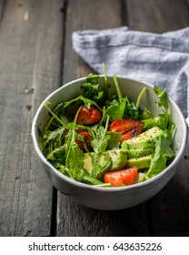 Useful tasty salad with arugula, fresh strawberries and avocado, seasoned with honey, wine vinegar, olive oil and poppy seeds on a vintage dark vintage background.
