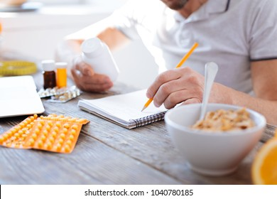 Useful tips. Selective focus of male hands taking white plastic bottle filled with pills while taking notes about biohacking