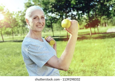 Useful tools. Enthusiastic energetic cheerful pensioner looking glad while exercising with new yellow hand weights