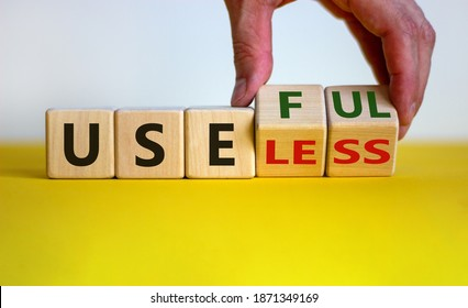 Useful or useless symbol. Male hand turns cubes and changes the word 'useless' to 'useful'. Beautiful yellow table, white background. Business and useful or useless concept. Copy space.