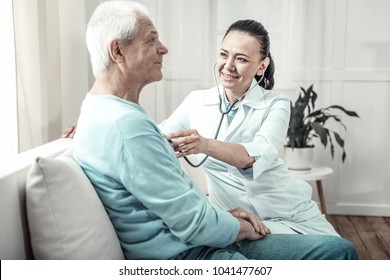 Useful utensil. Pleasant kind cute nurse sitting in the room near a man using her stethoscope and smiling.