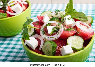 Useful vegetarian salad with raw tomatoes, cucumbers and onions on a green checkered tablecloth closeup