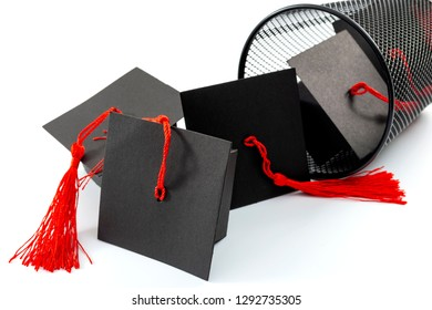 Useless university degree and collage is a waste of time and money concept theme with numerous graduation caps falling out of a trashcan or rubbish bin isolated on white background