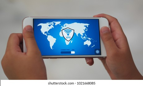 User holding mobile phone with an application connecting to a secure network via VPN (virtual private network)