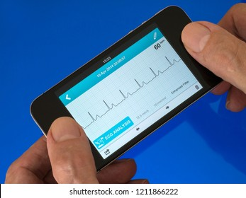User holding portable handheld ECG EKG Heart Monitor App running on mobile phone with trace showing normal sinus heart rhythm.