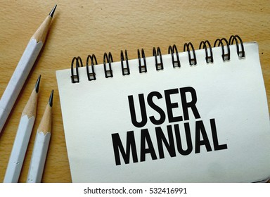User Manual text written on a notebook with pencils