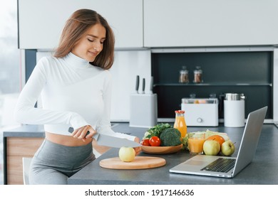 Uses laptop. Young european woman is indoors at kitchen indoors with healthy food.