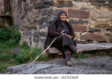 Ushguli; Georgia - 09.08.2019: elderly woman sits in front of the Svan tower with a wooden cane. Travel.