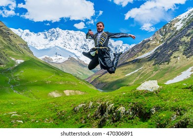 USHGULI, GEORGIA - MAY 22, 2016: The young Georgian man performs the jump element from the ethnic war dance in the national costume, on May 22 in Ushguli.