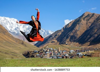 USHGULI, GEORGIA - OCTOBER 27, 2019: Georgian woman in local Svaneti costumes jumps and performs traditional dance, with mount Shkhara in the background, in Ushguli, Georgia