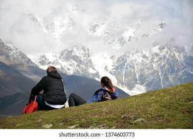 Ushguli, Georgia - October 3, 2018: Couple of tourists is looking to the mountains in village of Ushguli in Svaneti region