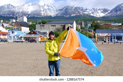 USHUAIA ARGENTINA 11 27 11: Man waving Tierra del Fuego flag in Ushuaia is the capital of Tierra del Fuego, Argentina. It is commonly regarded as the southernmost city in the world