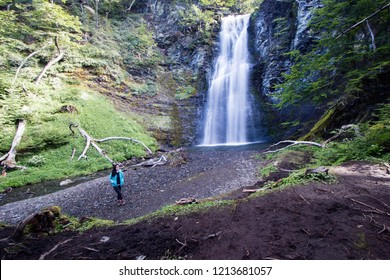 USHUAIA, ARGENTINA - FEBRUARY 11 2018: an unidentified woman in front of Submarino waterfall in Ushuaia, Tierra del Fuego island, Patagonia Argentina, South America