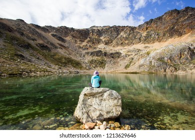 USHUAIA, ARGENTINA - FEBRUARY 14 2018: an unidentified person sitting on a stone by the Turquesa lagoon in patagonia Argentina, Ushuaia, Tierra del Fuego island, South America