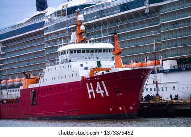 Ushuaia, Argentina-circa march, 2019: A red freighter ship anchored next to a transatlantic passenger ship in the city harbor. Beagle Channel, Patagonia.