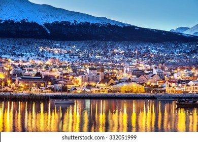 Ushuaia city in the late afternoon/night, lights on, lake in the foreground and snowed mountains in the background. Argentina, Patagonia, South America