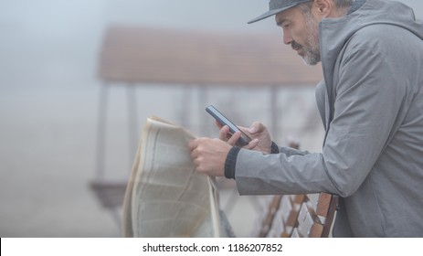 usiness, information, people and mass media concept - close up of male hands with newpaper, smart phone on a foggy rainy day at autumn beach