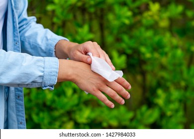 Using antibacterial wet wipes for cleaning and disinfection hands in park