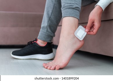 Using bactericidal medical adhesive plaster at home during wearing new shoe. Foot skin care and prevention of corns and calluses. First aid