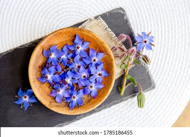 Using beautiful dark blue edible flower for food decoration Borago officinalis (Borago or borage). Flat lay view of blossoms in wood bowl on black stone plate, white background.