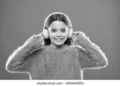 Using bluetooth wireless technology. Little child listening to music in bluetooth stereo earphones. Small girl wearing modern bluetooth headphones. Connecting bluetooth headset to her music player.