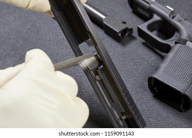 Using a bristle brush to clean the parts to a handgun with shallow depth of field