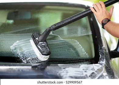 Using a brush to wash a car on a car washing facility on sunny summer day