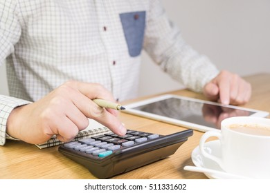 Using a calculator and tablet and making notes with a cup of coffee on a table