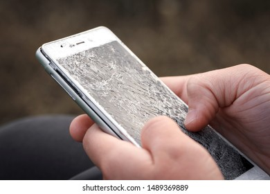 Using a cell phone with a broken screen. The protective glass of the smartphone with cracks. Female hands hold a damaged electronic gadget