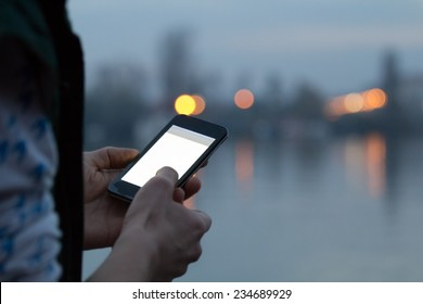 Using cellphone with defocused city lights and river reflection.