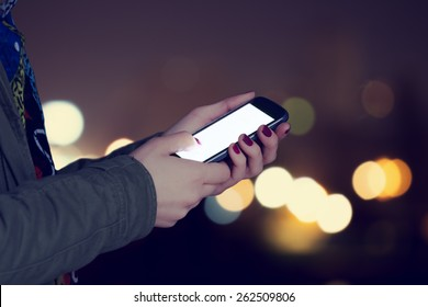 Using cellphone at night - with defocused city lights in the background.