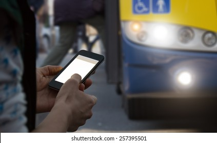 Using cellphone outdoors while waiting for the bus.