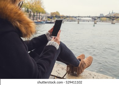 Using cellphone with Paris background and Seine river.