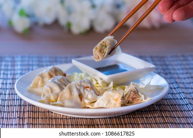 Using chopsticks to eat pork and vegetable Chinese potsticker dumplings with ginger soy dipping sauce