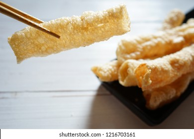 Using chopsticks to pick up deep fried bean curd robes or crispy tofu skin rolls from black plate placed on white painted wooden background. Vegan food for vegetarian festival. (selective focus)